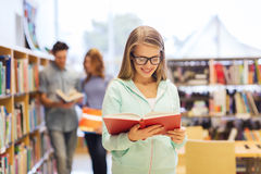 Happy student girl or woman with book in library Stock Photos