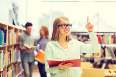 Happy student girl or woman with book in library Royalty Free Stock Images