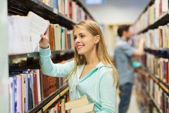 Happy student girl or woman with book in library Stock Photography