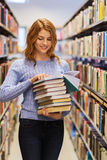 Happy student girl or woman with books in library. People, knowledge, education and school concept - happy student girl or young woman with stack of books in Royalty Free Stock Photography