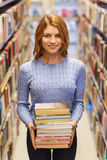 Happy student girl or woman with books in library Stock Photo