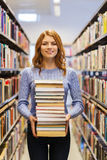 Happy student girl or woman with books in library Royalty Free Stock Photos
