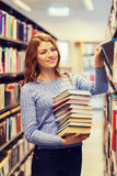 Happy student girl or woman with books in library. People, knowledge, education and school concept - happy student girl or young woman with stack of books in Stock Photos