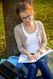 Happy student girl writing to notebook at campus Stock Image