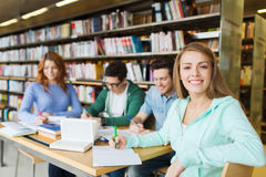 Happy student girl writing to notebook in library Royalty Free Stock Image
