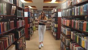 Happy student girl or young woman with book walking in library stock footage