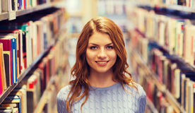 Happy student girl or young woman in library Stock Photos