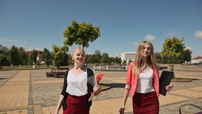 Happy student girls with abstracts talking a stroll in the Park on a Sunny day. In the background a fountain. Happy student girls with abstracts talking a stock footage