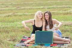 Happy student girls holding board for writing Stock Images