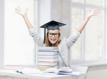Happy student in graduation cap. With stack of books Stock Photography