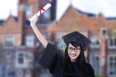 Happy student in graduation gown outdoor Royalty Free Stock Photo