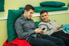 Happy student have a break in university. Have a good time while using phone , tablet and laptop. Two boys royalty free stock image