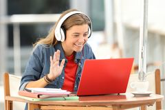 Happy student having a video conference in a bar. Happy student having a video conference with a red laptop and headphones sitting in a bar terrace Royalty Free Stock Photos