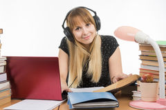 Happy student with headphones preparing for exams at the table looked at the frame Stock Photo