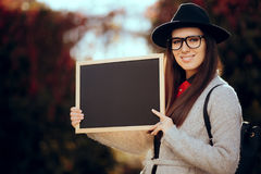Happy Student Holding a Blackboard Sign Sale Announcement. First school day concept image of a girl with blank board announcement in autumn décor Stock Photography