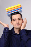 Happy student holding a pile of books on his head. Stock Images