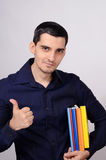 Happy student holding a pile of books under his arm signing thumbs up. Royalty Free Stock Photography