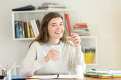 Happy student holding a vitamin pill on a desk. Happy student holding a vitamin pill supplement in a desk at home stock photography