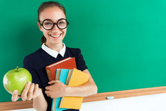 Happy student hugging books and gives an apple. Stock Images