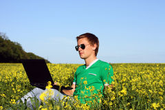 Happy student with laptop sitting at the grass. Young guy with a laptop sitting in a field Royalty Free Stock Photos