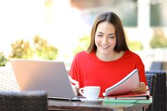 Happy student with a laptop studying reading notes royalty free stock photography