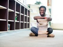 Happy Student Leaning On Stacked Books In Library. Full length portrait of happy African American student leaning on stacked books while sitting on floor at Royalty Free Stock Photo