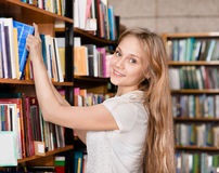 Happy student in the library surrounded by books.  Royalty Free Stock Photography