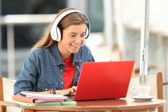Happy student listening a video tutorial on line. With a laptop sitting in a bar terrace stock photo