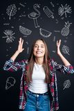 Happy student looking excited while thinking about exotic countries. Unbelievable. Cheerful smiling young student feeling happy and putting her hands up while royalty free stock image