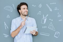 Happy student looking glad while being at the Math lesson. Easy mathematical problem. Cheerful enthusiastic young man being at the Math lesson and feeling happy royalty free stock image