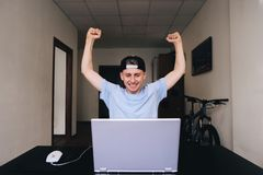 Happy student looking at a laptop and rejoicing while raising his hands up. Teen room. Stock Photo