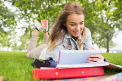 Happy student lying on the grass studying with her tablet pc Stock Image