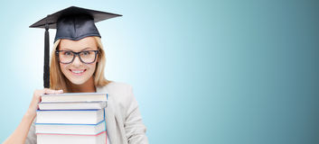 Happy student in mortar board cap with books Royalty Free Stock Photography
