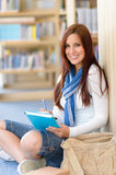 Happy student with notepad at high-school library. Female high school student at library sitting on the floor Royalty Free Stock Images