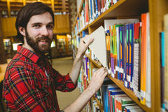 Happy student picking book in library Stock Images