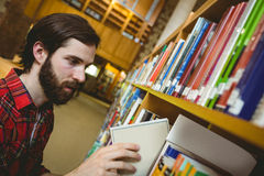 Happy student picking book in library. At the university Stock Photo