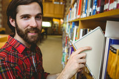 Happy student picking book in library. At the university Stock Photography