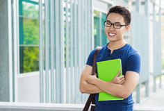 Happy student. Portrait of happy Vietnamese student with a textbook Stock Photography
