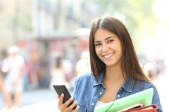 Happy student posing holding a smart phone. Happy student posing looking at camera holding a smart phone and folders in the street Stock Photography