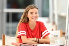 Happy student posing in a restaurant terrace. Happy student posing and looking at camera sitting in a restaurant terrace Royalty Free Stock Photography