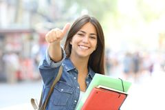 Happy student posing with thumbs up in the street. Happy student posing with thumbs up looking at you in the street Royalty Free Stock Photos