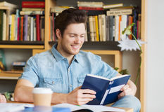 Happy student reading book and drinking coffee Royalty Free Stock Photo