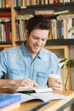 Happy student reading book and drinking coffee Stock Photos