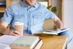 Happy student reading book and drinking coffee Royalty Free Stock Photography