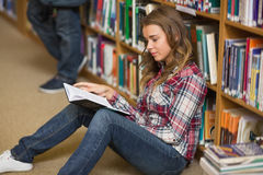 Happy student reading book on library floor Royalty Free Stock Images
