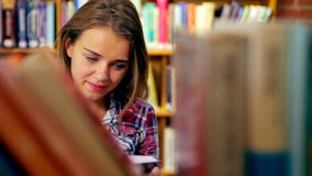 Happy student reading book standing in the library. In college stock video footage