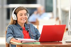 Happy student relaxing watching on line content. With a red laptop sitting in a bar terrace royalty free stock images