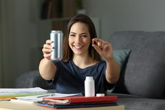 Happy student showing energy drink and vitamin pill. Front view portrait of a happy student showing energy drink and vitamin pill in the night at home Royalty Free Stock Photo