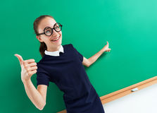 Happy student showing her thumb up and points to something. Royalty Free Stock Image
