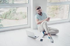 Happy student is sitting on the floor at home relaxing with cup. Of tea. He seats near the windows in pure light room Stock Photography